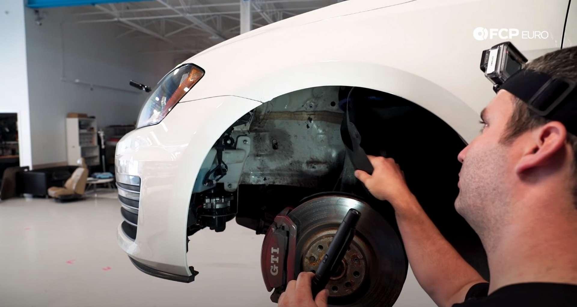 DIY VW GTI Hood Release peeling back the fender liner