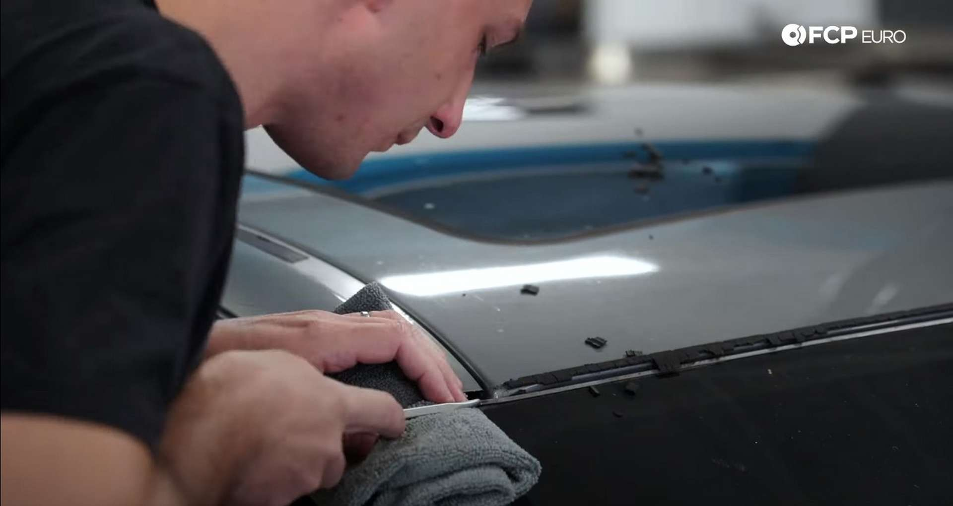 DIY BMW E9X Windshield Replacement lifting the corner of the metal strip