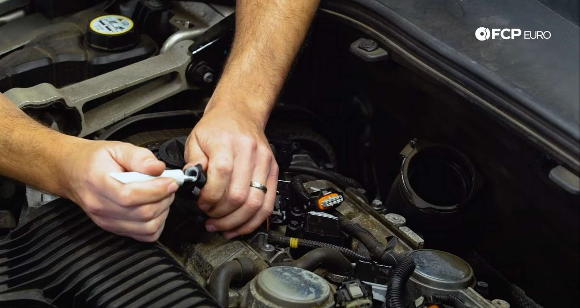 DIY Volvo Spark Plug and Ignition Coil Replacement placing the dielectric grease onto the ignition coil