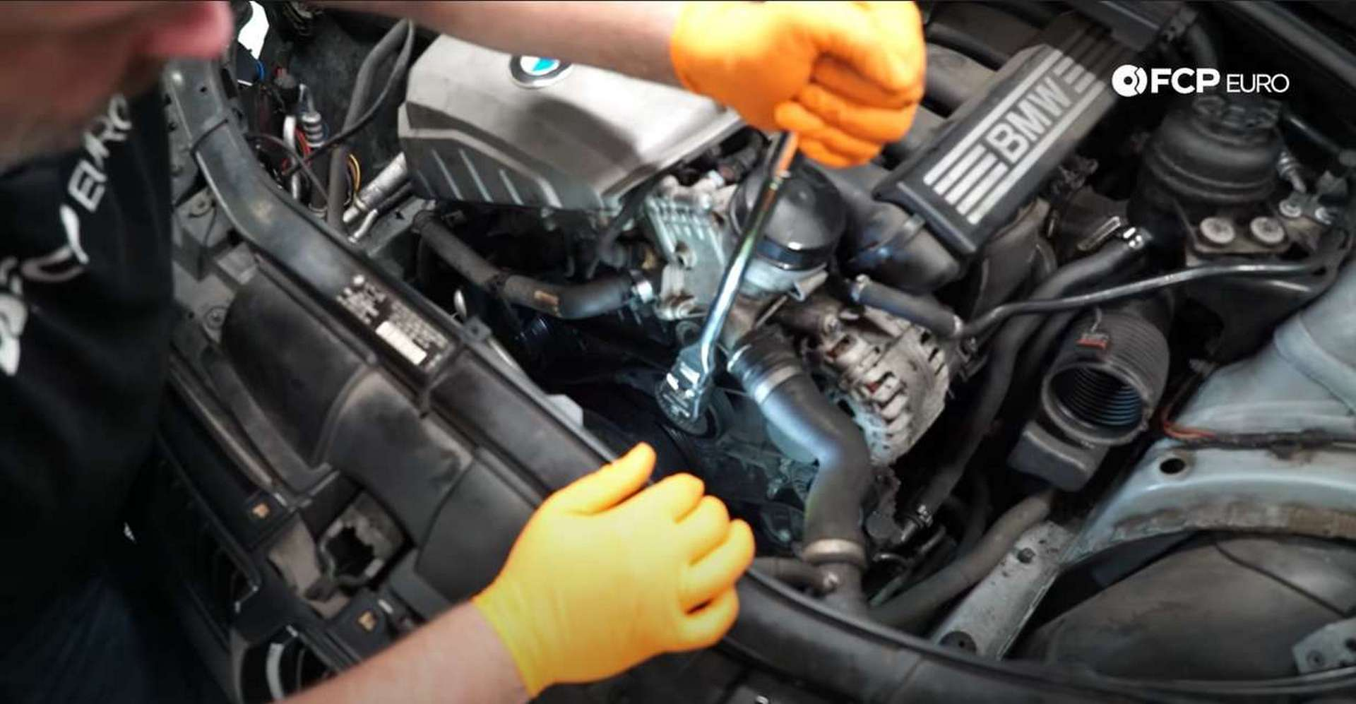 DIY BMW N52 Drive Belt Replacement releasing the tensioner's tension and removing the belt