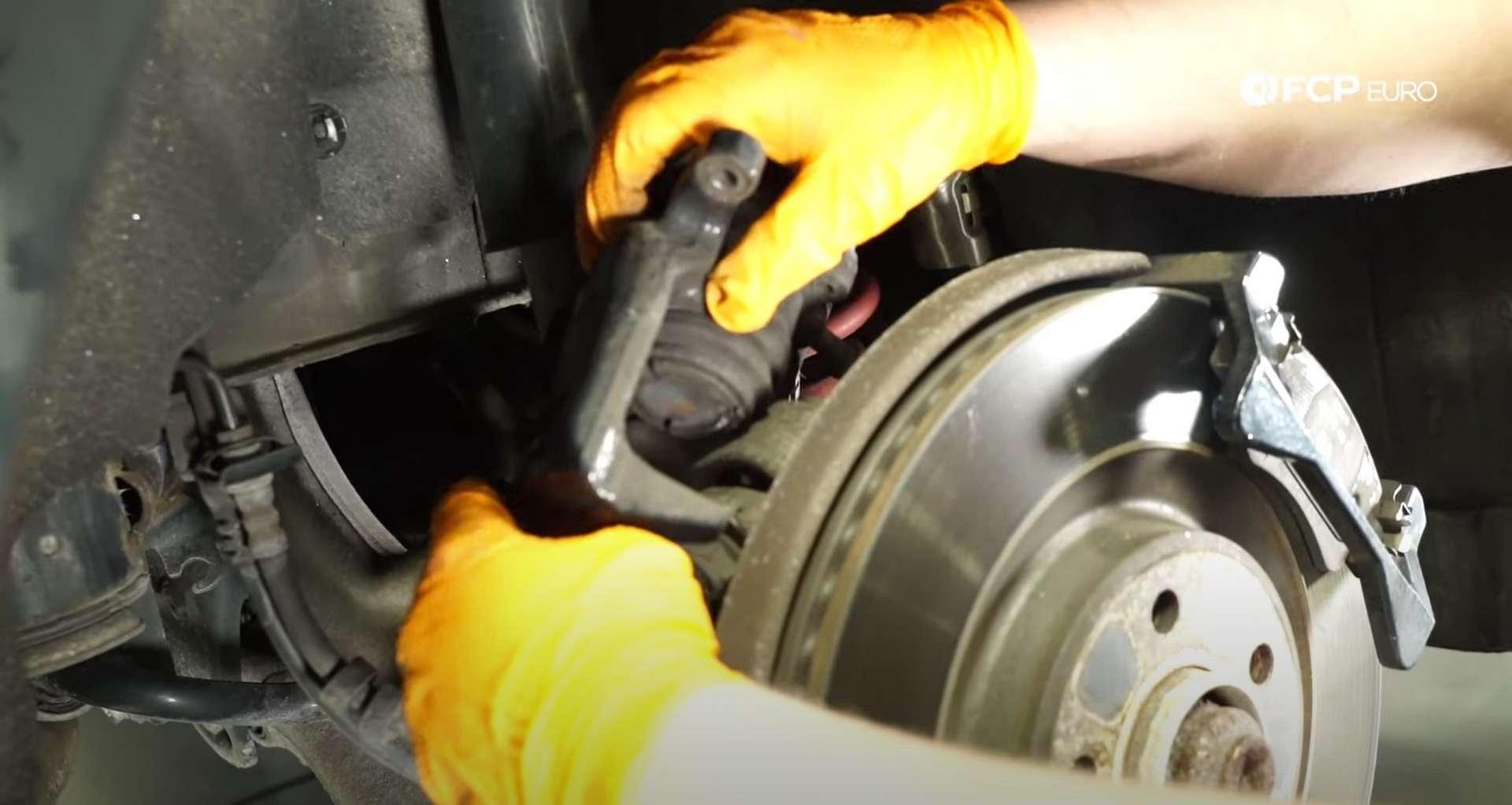 DIY Audi B8 S4 Rear Brake Service resting the caliper on the suspension