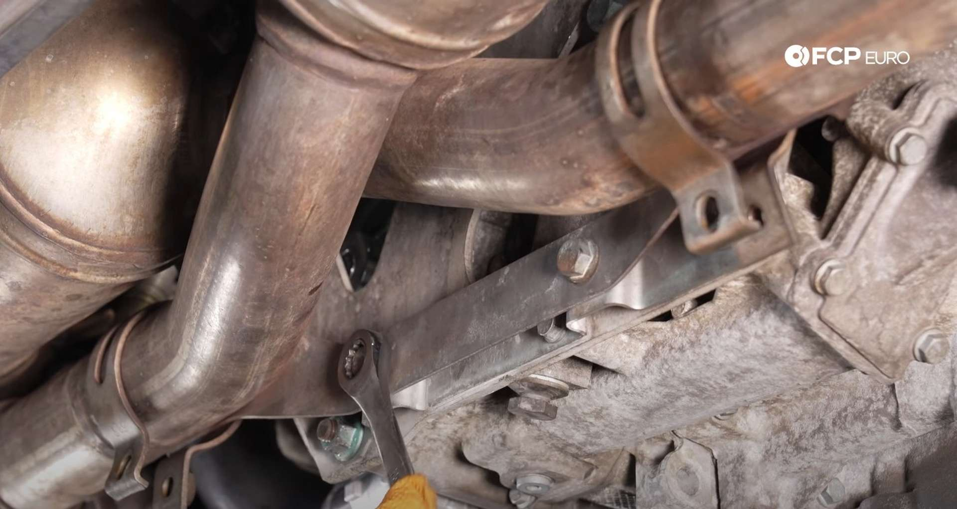 DIY Porsche 996 911 Water Pump And Thermostat Replacement tightening the exhaust bracket's bolts