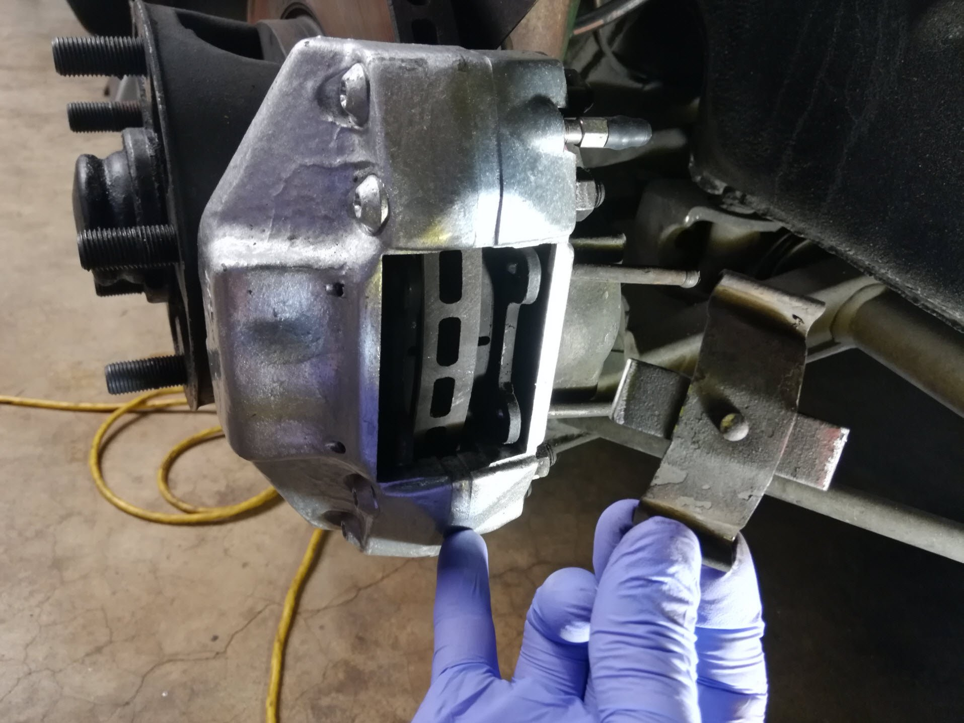Air-cooled Porsche 911 brake pad retaining spring removal.