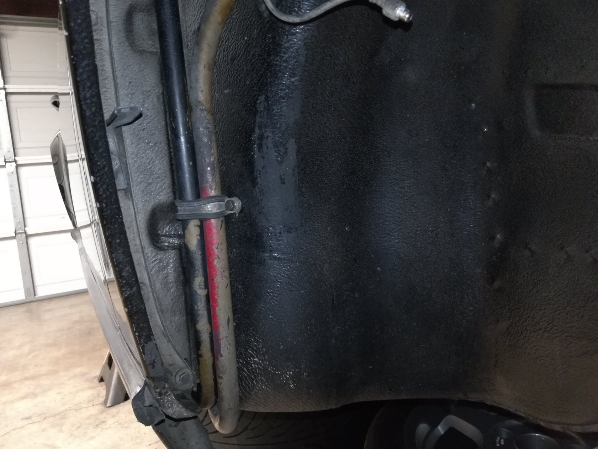 Air-cooled Porsche 911 hard oil line clamp under front fender well.